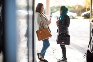 students talking at entrance to university