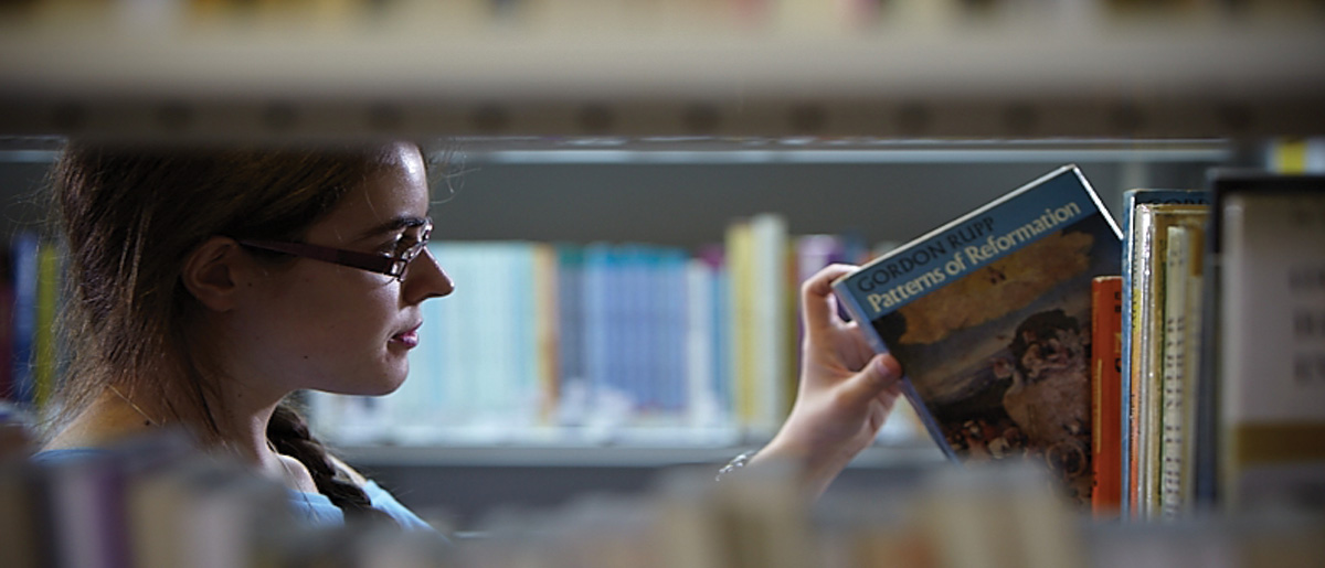 student picking book