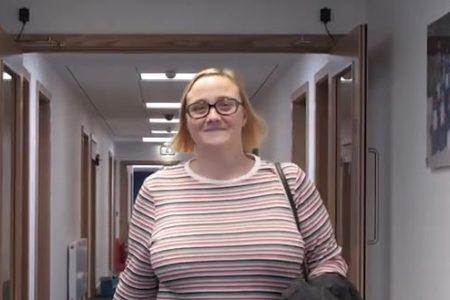 student marilyn walking down the corridor smiling at camera