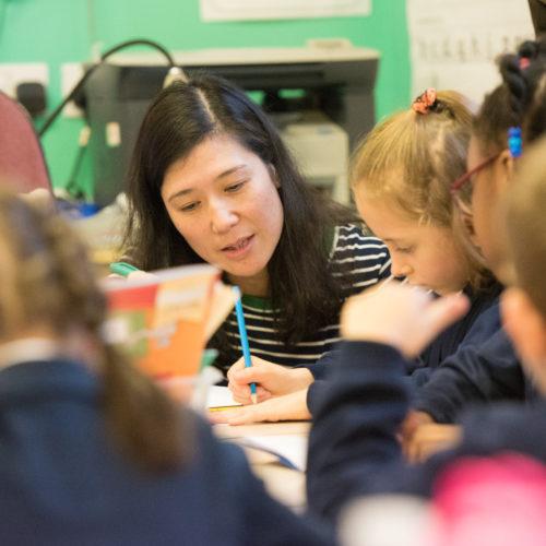 primary school teacher talking to children
