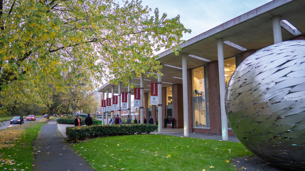Newman front of campus with welcome flags