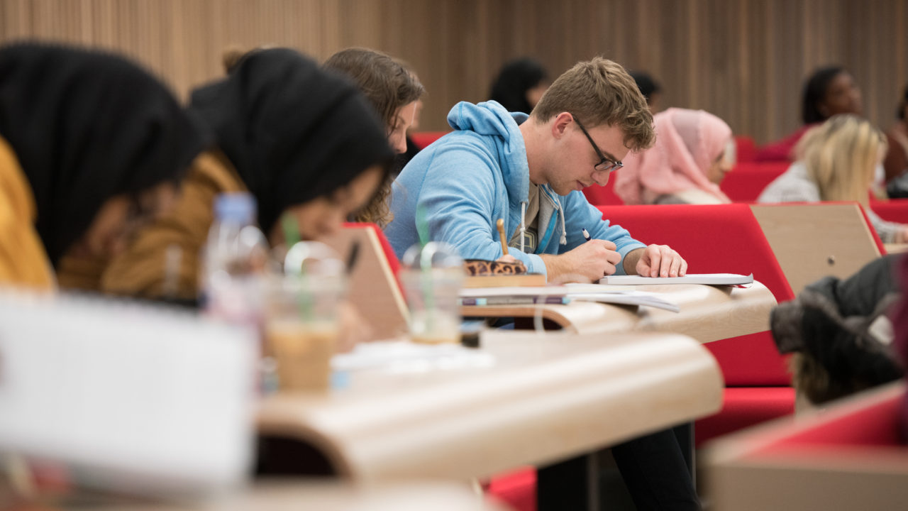 student writing in lecture theatre