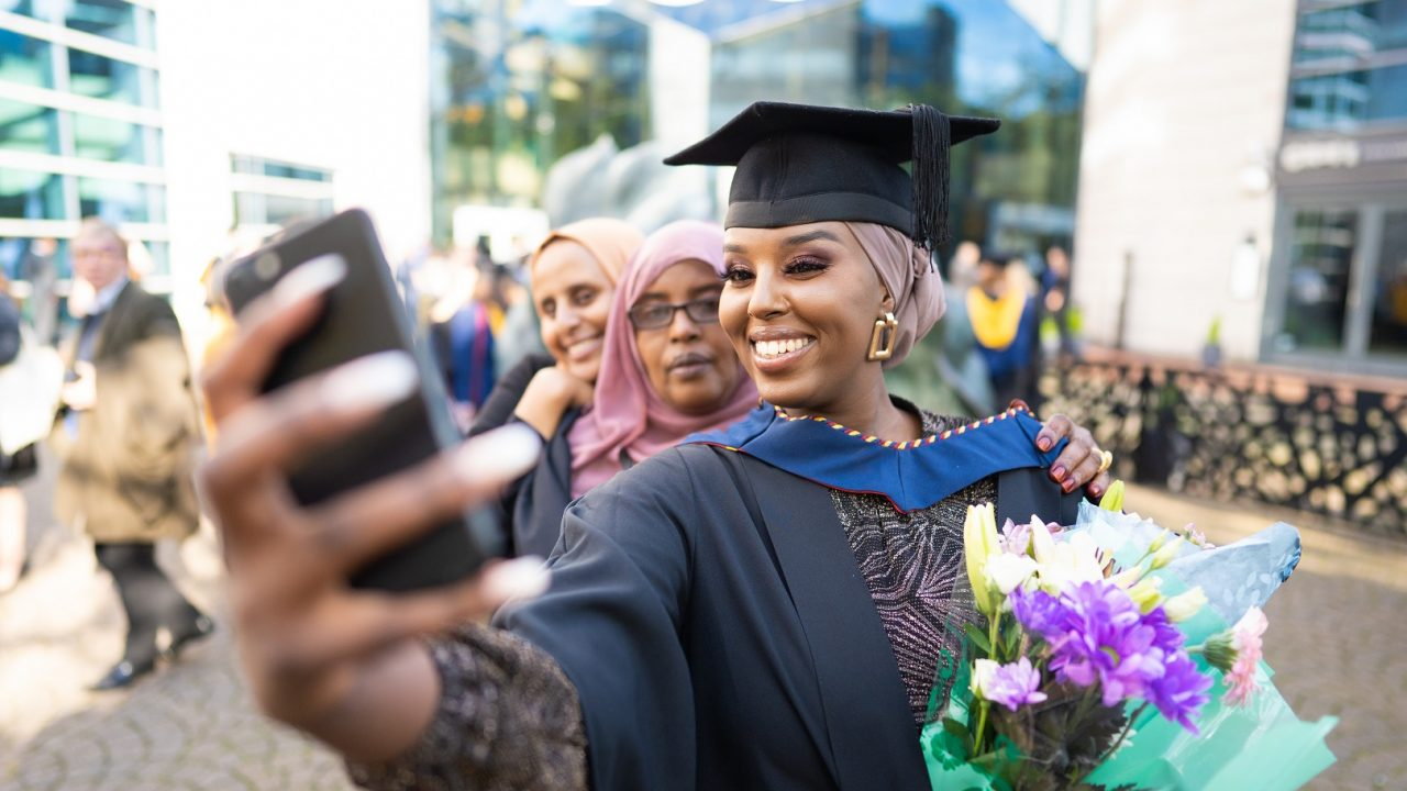 graduates taking a selfie on their phone