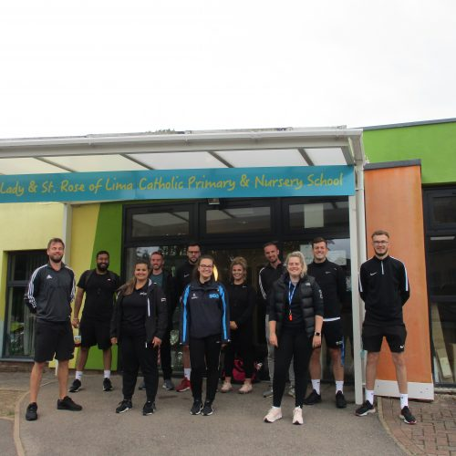 PGCE PE students standing outside a local primary school