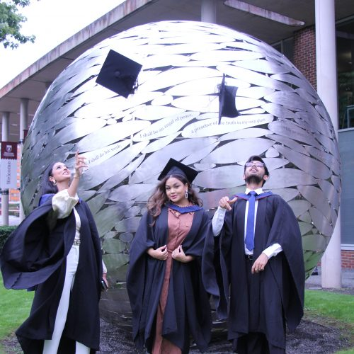 graduates throwing hats by the globe